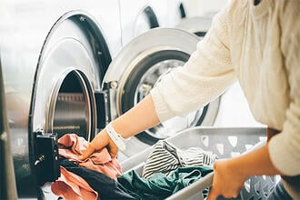 Girl loading dirty clothes inside a commercial washer