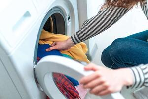 Loading colored clothes and linen in washing machine