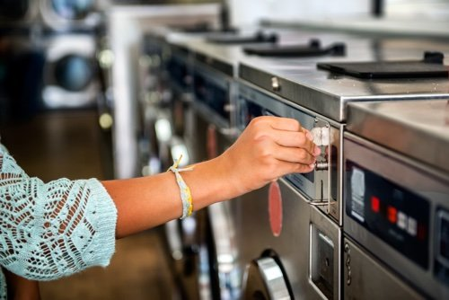 woman inserting coin into laundry machine